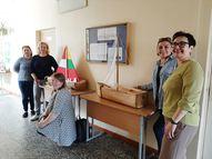 Abu skolu skolotājas pie   partneru izveidotajiem kuģiem no raupjas koka sagataves